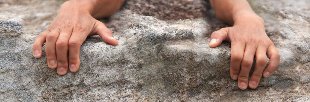 Rock climbers hands holding onto edge
